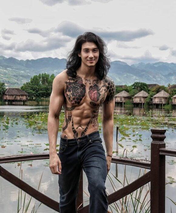 Paing Takhon posando con cabello largo suelto, jeans oscuros y el pecho descubierto