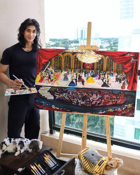 Paing Takhon vistiendo camisa y pantalón negro posando junto a caballete con un cuadro recién pintado