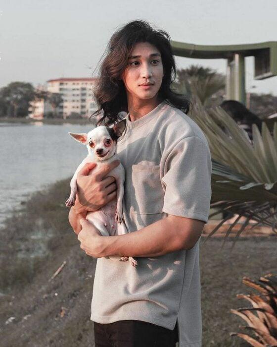 Paing Takhon con playera gris sosteniendo un perro chihuahua blanco