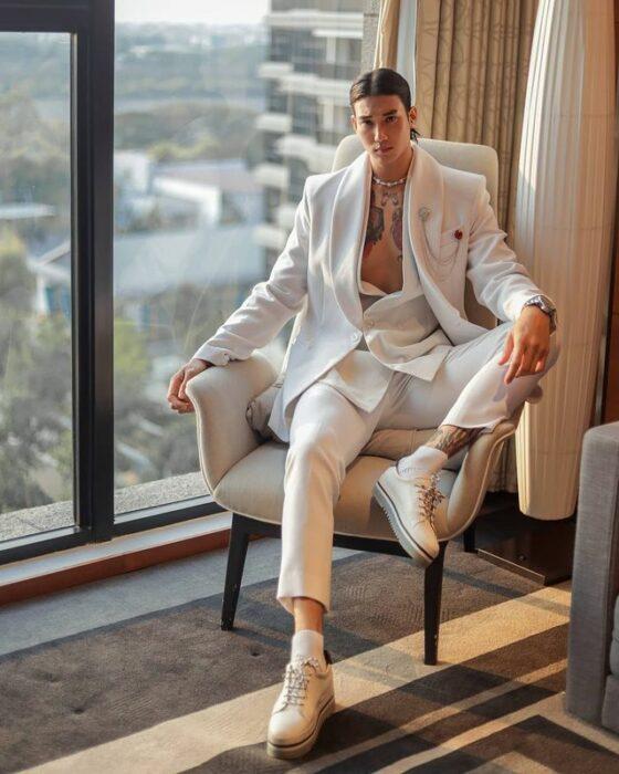 Paing Takhon sentado en un sillón con un traje blanco y tenis blancos