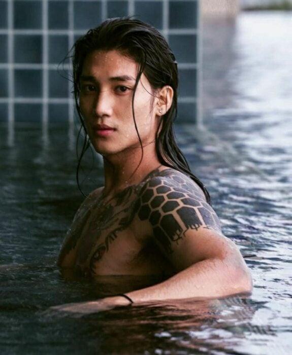 Paing Takhon sin playera en una piscina con el cabello mojado mirando a la cámara