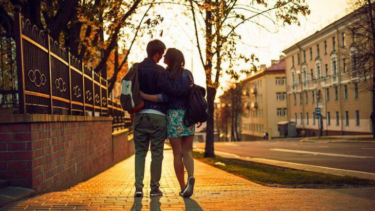 Pareja caminando mientras se abrazan