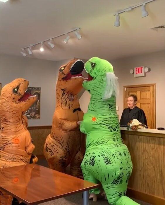 Pareja en la corte casándose con disfraz de dinosaurios