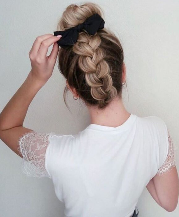 Brown-haired girl with braid in the never and high bun