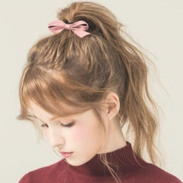 Girl with light brown hair, with a casual ponytail with bangs and a pink ribbon as an ornament
