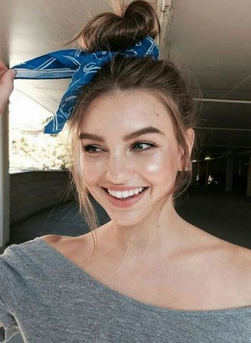 Chica llevando un bun alto con pañoleta azul; Peinados para cuando acabas de bañarte