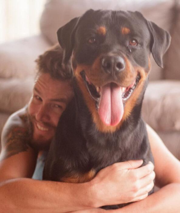 Perros sonriendo; perrito adulto rottweiler con su dueño abrazándolo
