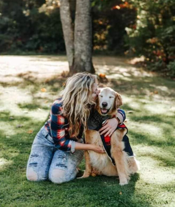 Perros sonriendo; perrito viejito golden retriever con canas y su dueña abrazándolo en el parque