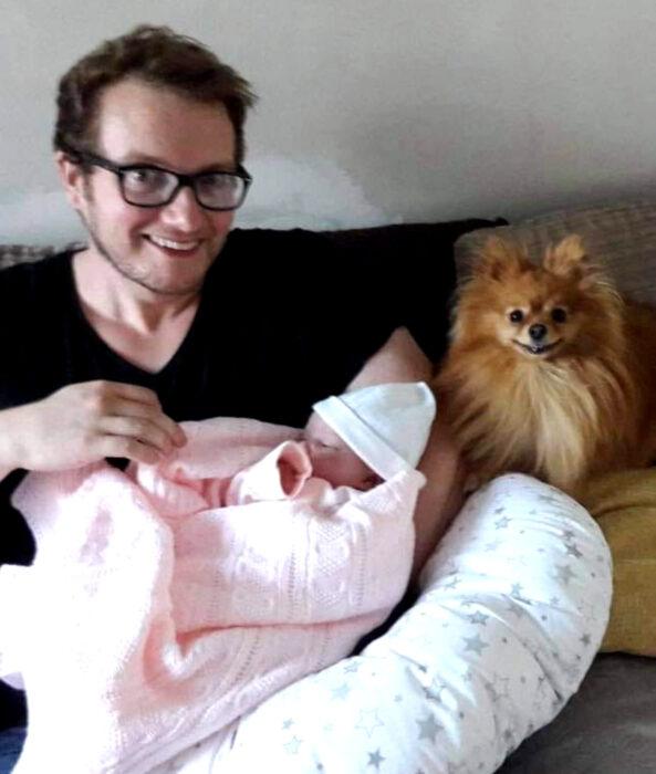 Perros sonriendo; perrito pomerania oeludo color café con dueño y bebé