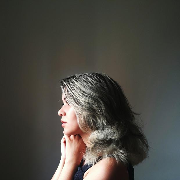 Chica posando de perfil con cabello suelto con canas a la altura de los hombros