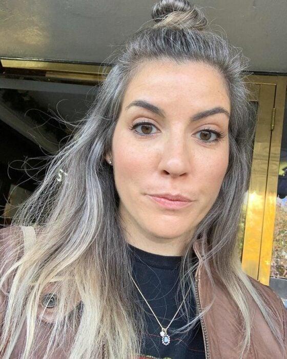 Chica blanca de ojos cafés con cabello largo con canas recogido en un medio chongo