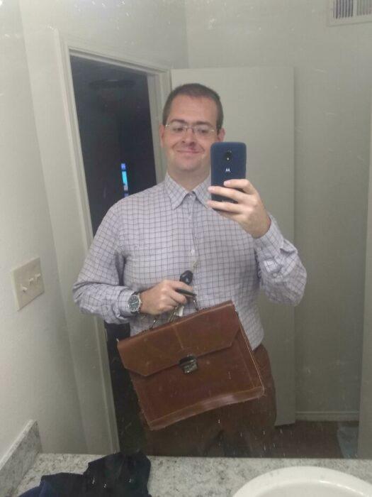 Hombre usando camisa y portafolio tomándose una foto en el espejo