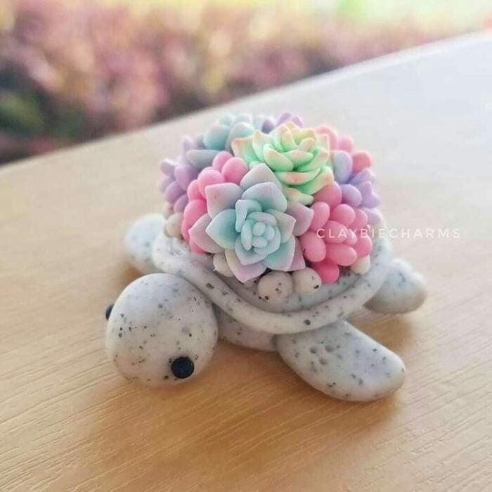 Tortuga gris con suculentas verdes y rosas hecha con arcilla polimérica