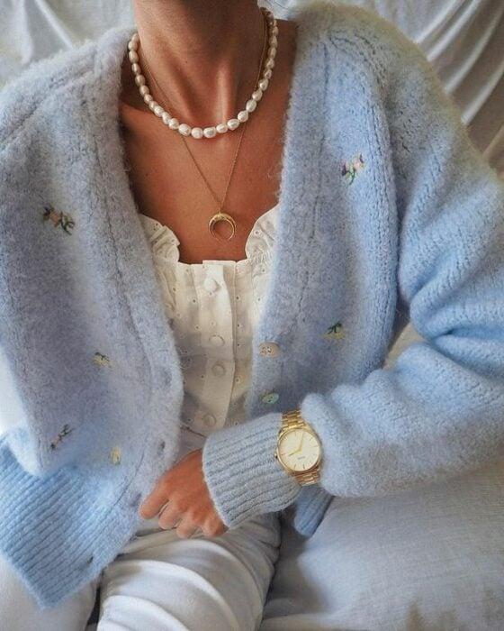 Chica con jeans claros, blusa blanca y suéter de punto con botonescolor azul