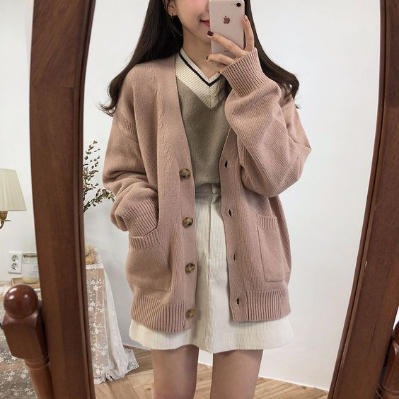 Asian girl taking selfie in front of the mirror with white corduroy skirt, gray sweater and another pale pink sweater on top with tortoiseshell buttons