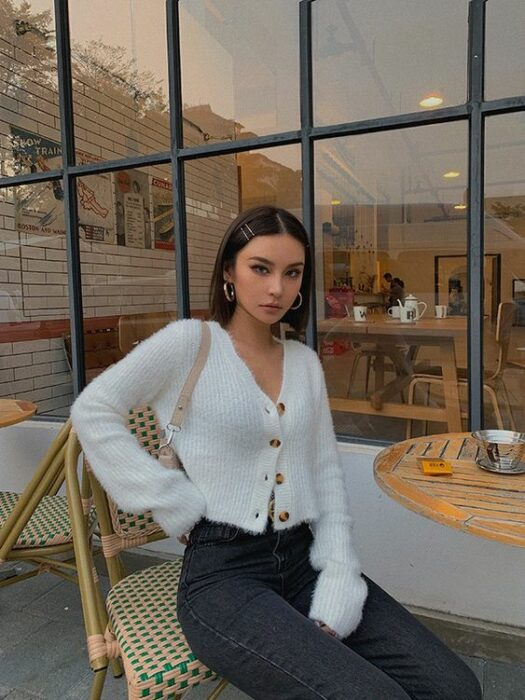 Slim girl sitting at a table outside the cafeteria wearing black pants, white sweater with brown buttons and very short long hair with side clips