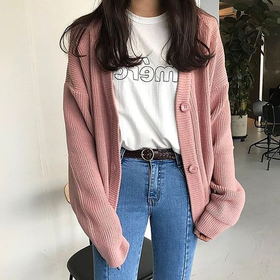 Dark haired Asian girl wearing dark jeans, white blouse and long pink sweater knitted with pink buttons