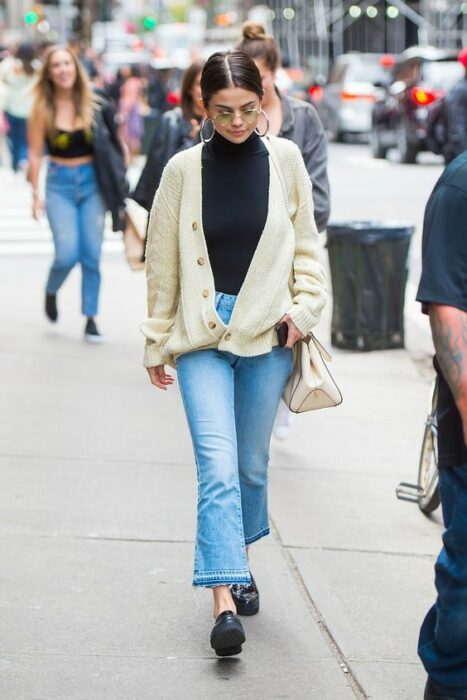 Selena Gómez walking in the street wearing flared jean pants, black shoes, black collared blouse and long knitted sweater with beige buttons