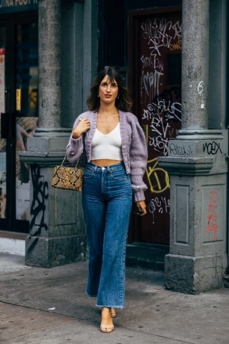 Parisian girl in flared jeans, high-heeled sandals, white blouse and purple knitted sweater with wide sleeves