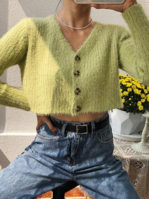 Girl with blue jeans, black belt, green knitted sweater with tortoiseshell buttons and a silver chain around her neck