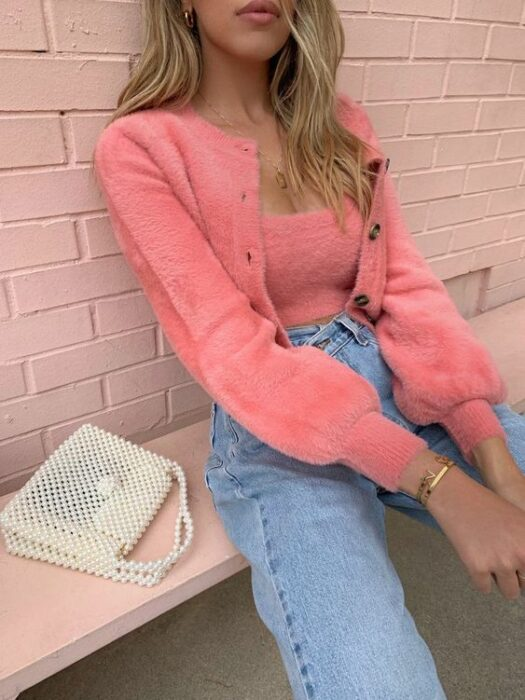 Blonde girl sitting on a bench wearing light jeans at the waist with knitted sweater and blouse with brown buttons