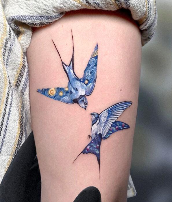 Tatuaje bonito y femenino de ave en el brazo, pájaros golondrinas volando fusionados con La noche estrellada de Vincent Van Gogh