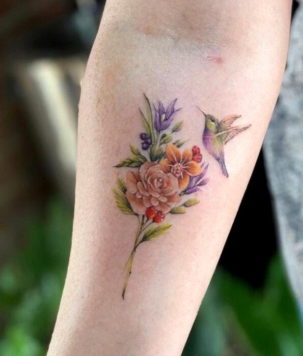Tatuaje bonito y femenino de ave en el brazo, pájaro colibrí volando sobre flores
