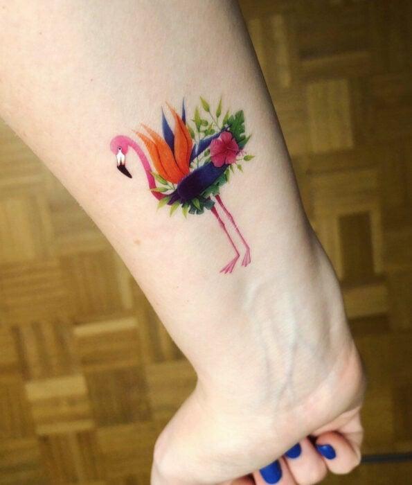 Tatuaje bonito y femenino de ave en la muñeca, pájaro flamenco con flores