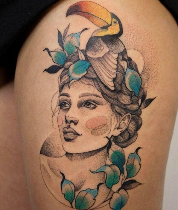 Tatuaje bonito y femenino de ave en la pierna, pájaro tucán en la cabeza de una mujer, puntillismo