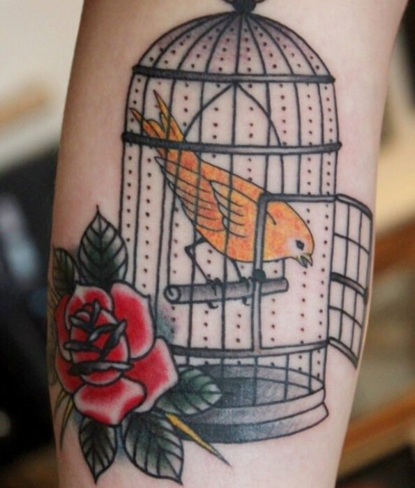 Pretty and feminine bird tattoo on the calf, canary bird in an open cage with a traditional rose