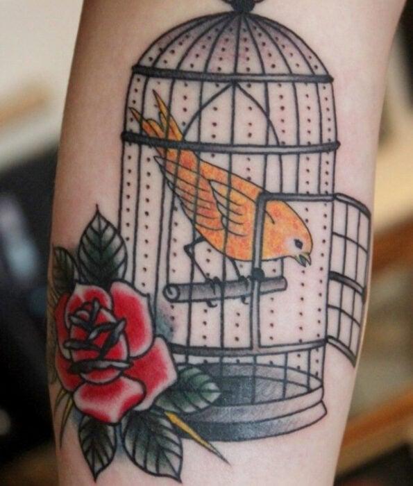 Tatuaje bonito y femenino de ave en la pantorrilla, pájaro canario en una jaula abierta con una rosa tradicional
