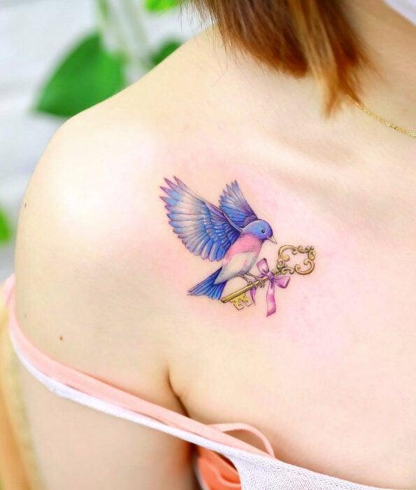 Tatuaje bonito y femenino de ave en la clavícula, pájaro azulejo volando con una llave antigua