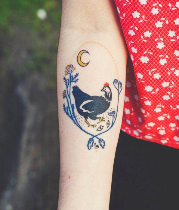 Tatuaje bonito y femenino de ave en el brazo, pájaro gallo con flores y luna creciente