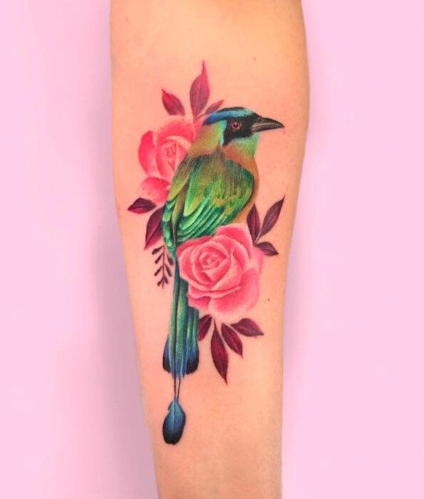 Tatuaje bonito y femenino de ave en el brazo, pájaro barranquero verde con flores rosas