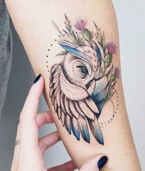 Tatuaje bonito y femenino de ave en el brazo, pájaro búho con flores