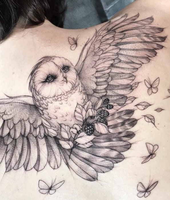 Tatuaje bonito y femenino de ave en la espalda, pájaro lechuza volando