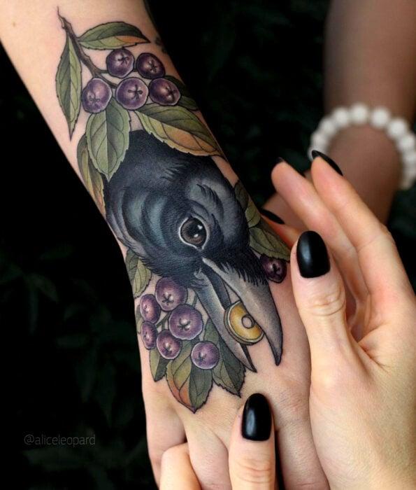 Tatuaje bonito y femenino de ave en la mano y muñeca, pájaro cuervo con moneda de oro en el pico