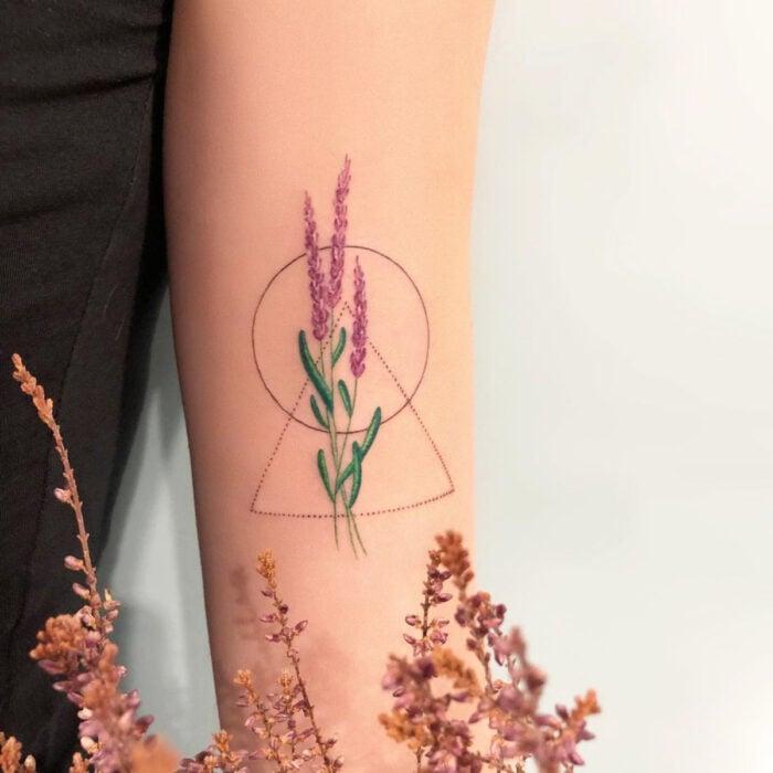 Tatuajes bonitos, pequeños y femeninos; tatuaje de espiga de lavanda con figuras geompetricas, círculo y triángulo en el brazo