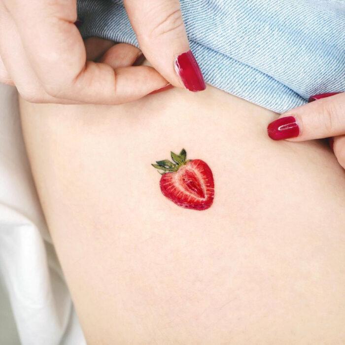 Tatuajes bonitos, pequeños y femeninos; tatuaje minimalista de fresa partida a la mitad en la pierna