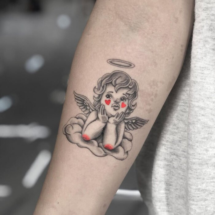 Pretty, small and feminine tattoos; Cherub tattoo with hearts on the cheeks, on the arm