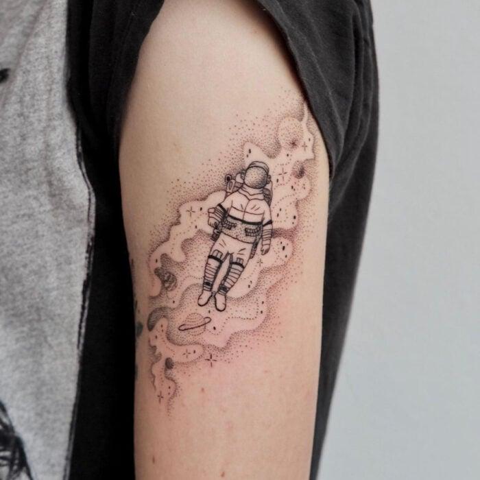 Tatuajes bonitos, pequeños y femeninos; tatuaje de astronauta en el espacio con técnica de puntillismo en el brazo