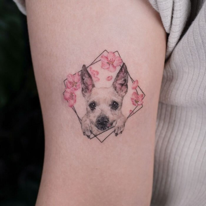 Pretty, small and feminine tattoos; Dog tattoo with pink flowers on the arm