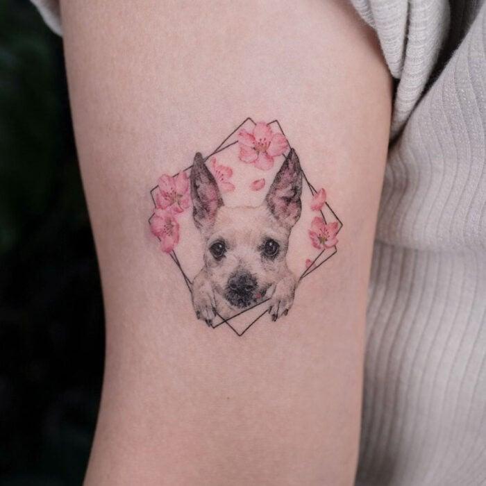 Tatuajes bonitos, pequeños y femeninos; tatuaje de perro con flores rosas en el brazo