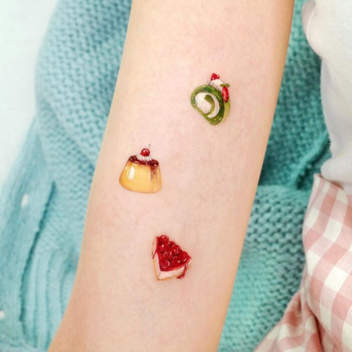 Tatuajes bonitos, pequeños y femeninos; tatuaje de postres minimalistas, flan, roll y pay en el brazo