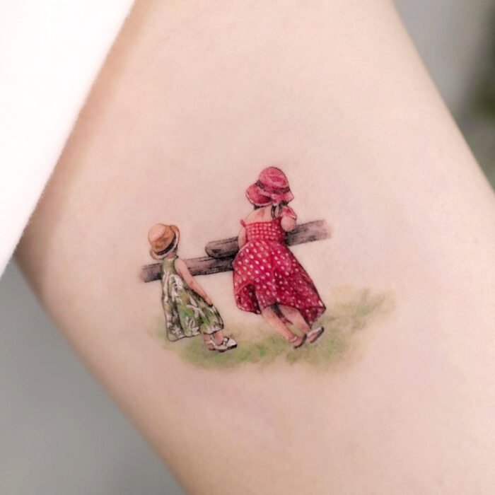 Pretty, small and feminine tattoos; Portrait tattoo of girls in the field with green and red dresses, on the arm