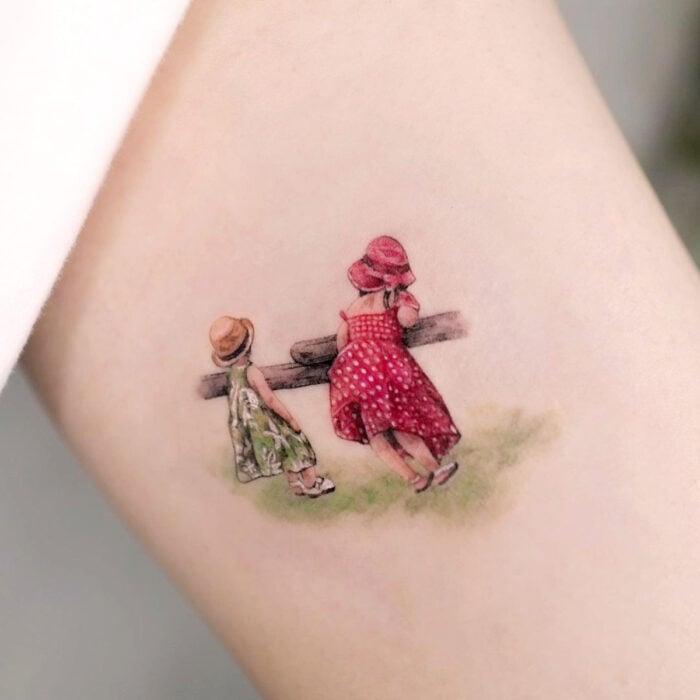Tatuajes bonitos, pequeños y femeninos; tatuaje de retrato de niñas en el campo con vestidos verde y rojo, en el brazo