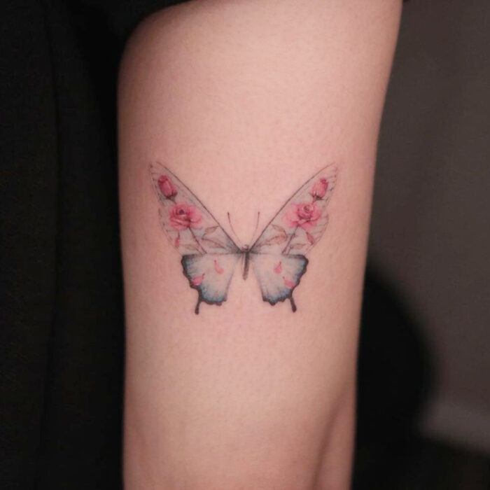Tatuajes bonitos, pequeños y femeninos; tatuaje de mariposa con alas de flores rosas en el brazo