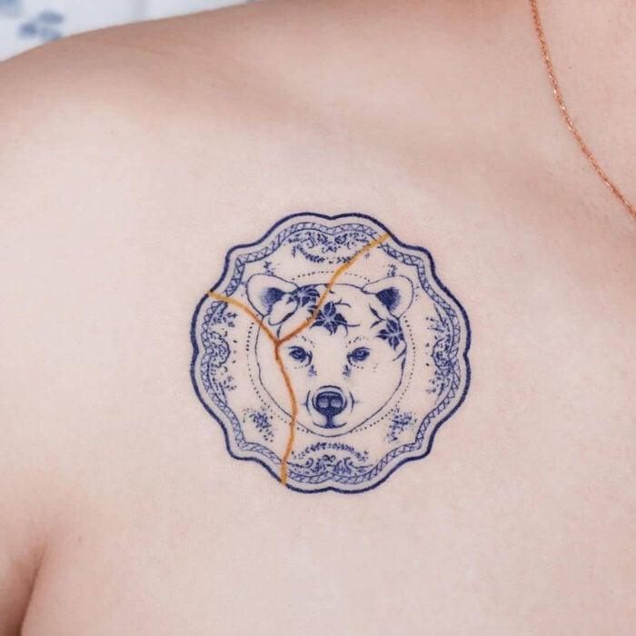 Tatuajes bonitos, pequeños y femeninos; tatuaje estilo japonés, de vajilla azul con cara de oso, kintsugi en las clavículas