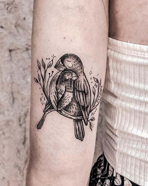 Tatuaje en el brazo para mamás de ave con su cría en una rama