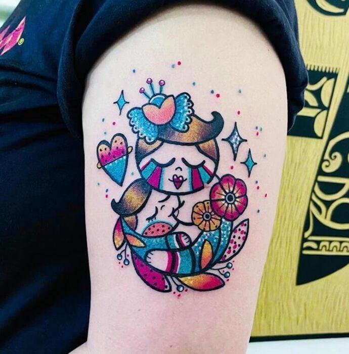 Tatuaje colorido en el brazo de madre amamantando a su hijo